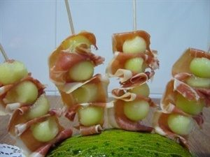 a. Ingredientes para ocho personas: 1 melón de galicia maduro, 6 lonchas finas de jamón serrano de hembra, palitos de pincho. b. Preparación: Pelar y cortar el melón en daditos iguales. A continuación, cortar por la mitad las lonchas de jamón, e ir enrollando cada trozo de jamón con el de melón. Pinchar en cada trocito de melón con jamón con un palito a la hora de servir. Servir frío.